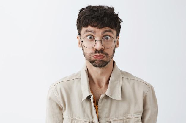 Ragazzo barbuto elegante divertente che posa contro il muro bianco con gli occhiali