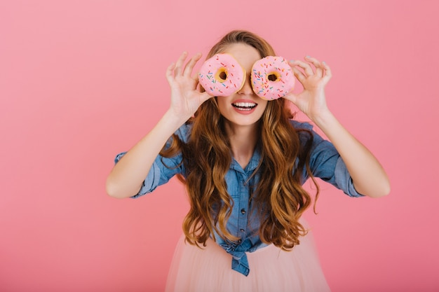 Funny stylish girl in trendy outfit fools around with delicious donuts which she bought at the bakery for tea. portrait of graceful curly young woman posing with sweets isolated on pink background