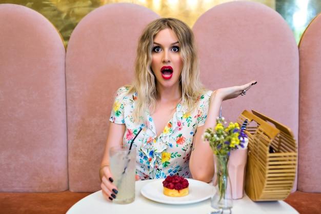 デザートを食べるかわいいカフェでポーズをとる金髪の女性の面白いスタイリッシュな肖像画、クレイジーな驚きの感情、ダイエットコンセプト、ピンナップスタイル。