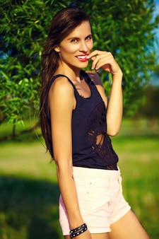 公園で夏の明るい流行に敏感な布で面白いスタイリッシュなセクシーな笑顔美しい日光浴若い女性モデル