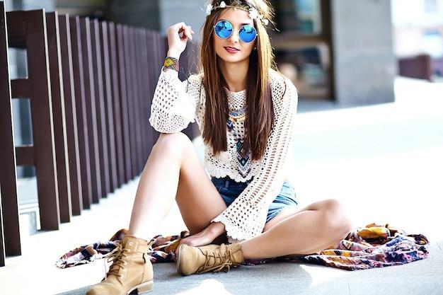 通りでポーズをとって夏白い流行に敏感な服で面白いスタイリッシュなセクシーな笑みを浮かべて美しい若いヒッピー女性モデル