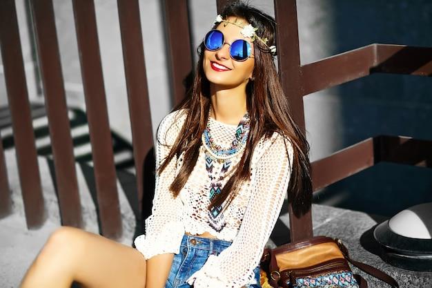 通りに座っている夏の白い新鮮な流行に敏感な服で面白いスタイリッシュなセクシーな笑顔美しい若いヒッピー女性モデル
