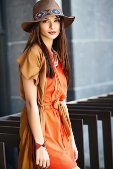 Funny stylish sexy smiling beautiful young hippy woman model in summer bright hipster clothes dress in the street in hat