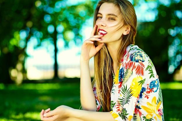 Смешная стильная сексуальная улыбающаяся красивая модель молодой женщины в летнем ярком платье из ткани битника на улице