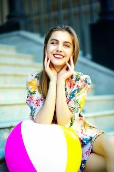 Смешная стильная сексуальная улыбающаяся красивая модель молодой женщины в летнем ярком платье из ткани битника, сидящего на улице с разноцветным шариком