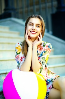 Funny  stylish sexy smiling beautiful young woman model in summer bright hipster cloth dress sitting in the street with colorful ball