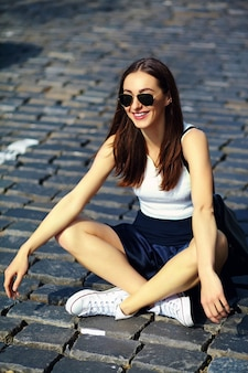 Funny stylish sexy smiling beautiful young woman model in summer bright hipster cloth sitting in the street