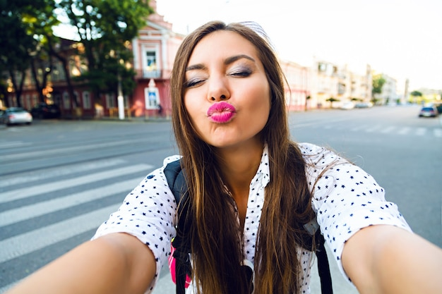 Divertente immagine estiva della ragazza giovane e carina che fa selfie per strada, inviandoti un bacio, umore positivo