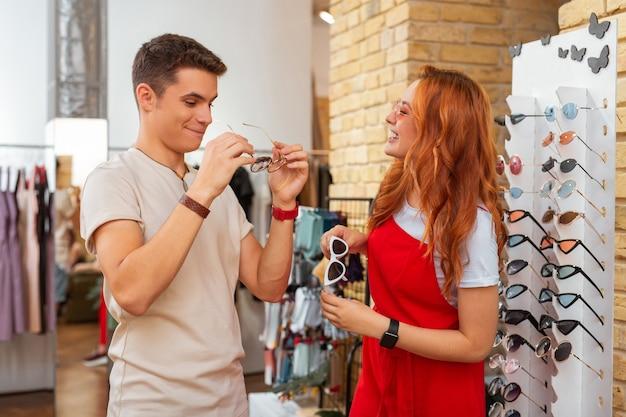 Забавные солнцезащитные очки. позитивная улыбающаяся красивая девушка ласково смотрит на своего парня, стоя рядом с ним в магазине и выбирая очки