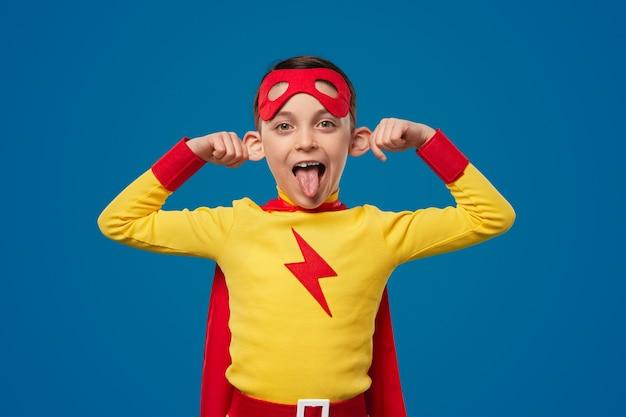 顔を作る面白いスーパーヒーローの少年