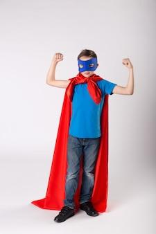 재미있는 슈퍼히어로 아이가 근육을 보여줍니다.