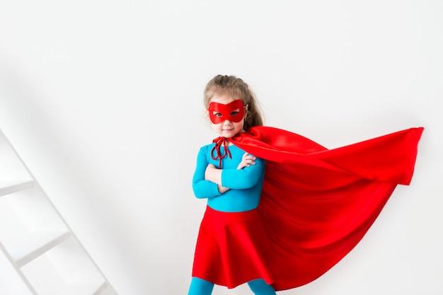 Забавный ребенок супергероя играет супергероев изолированы