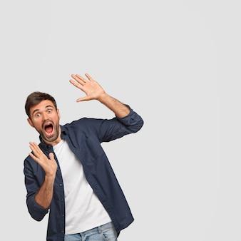 Забавный удивленный изумленный мужчина широко открывает рот, жестикулирует руками, замечает что-то чудесное, носит повседневную футболку и темно-синюю рубашку, позирует на фоне белой стены
