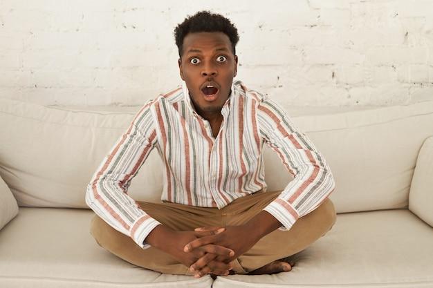 Забавно удивленный изумленный молодой африканский мужчина в повседневной одежде сидит на диване в позе полулотоса