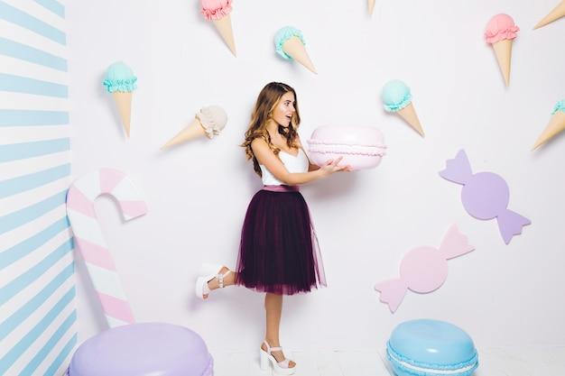 面白い驚きの魅力的な若い女性がアイスクリームの中で巨大なマカロンを保持しています。ポジティブ、ダイエットのコンセプト、夏の時間を表現する幸せな甘い瞬間。