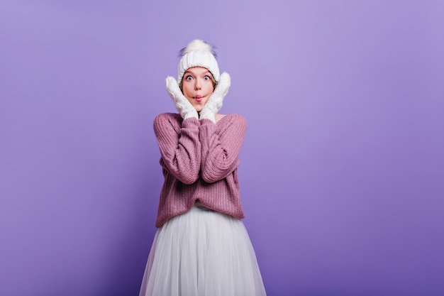 Funny surprised girl in winter attire touching her face. wonderful white woman in woolen clothes expressing amazement.