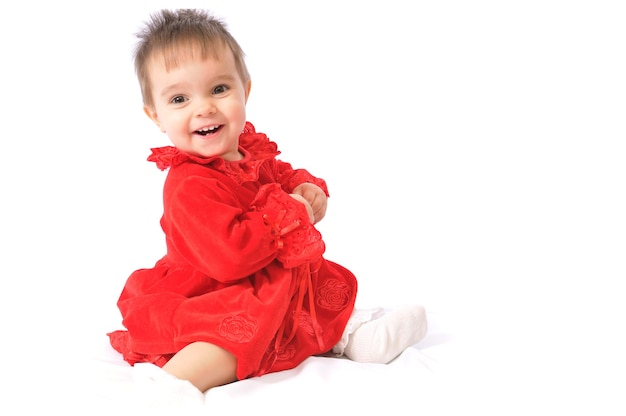 Funny surprised little girl in red christmas dresses on white