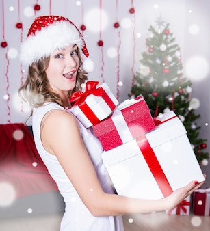 Funny surprised woman in santa hat with gift boxes near christmas tree