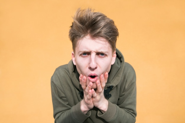 Funny surprised young man stands on an orange wall