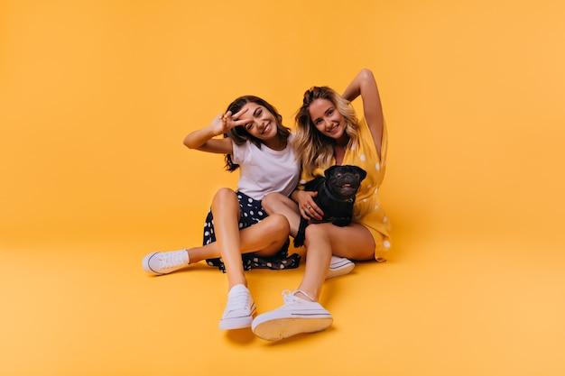 Divertenti ragazze abbronzate in posa sul pavimento con il cane. ritratto di splendide sorelle bianche isolate su giallo con bulldog francese.