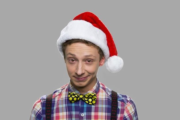 크리스마스 모자에 재미있는 십 대 소년. 산타 모자와 회색 배경에 카메라를보고 체크 무늬 셔츠에 백인 십 대 남자.