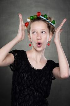 카메라 앞에서 장난을 치는 그녀의 머리에 과자 화환을 가진 재미있는 십대 소녀.