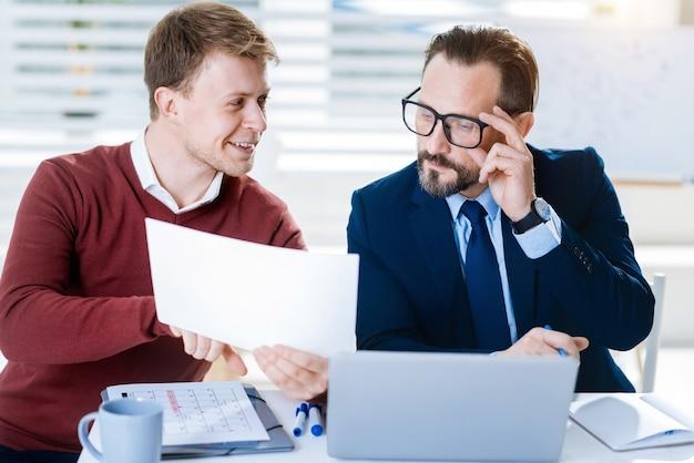 재미있는 것. 문서와 안경을 만지는 남자를 검사하는 동안 직장에서 나오는 매력적인 두 남성 동료