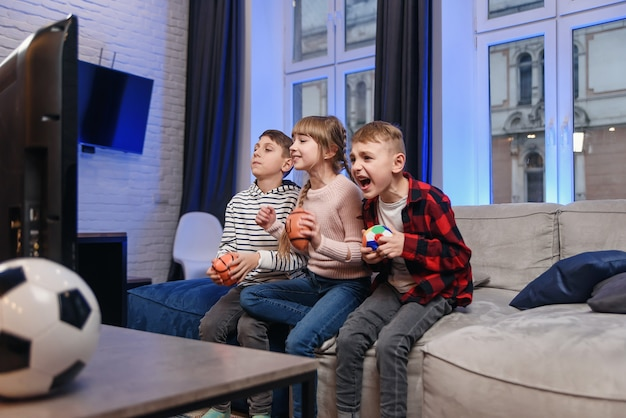 面白い3人の子供の友人が自宅のソファに座ってサッカーの試合を楽しんでいます。