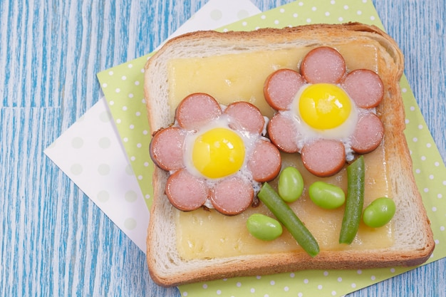 ソーセージ、インゲン、ウズラの卵で作られたチーズと花の面白いトースト