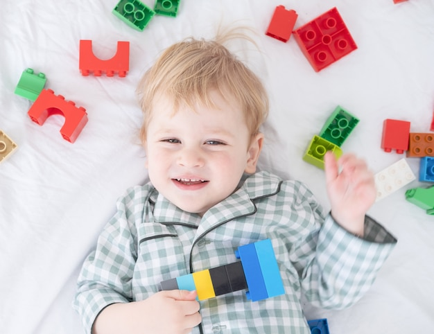 Funny toddler boy lying on white bed in pajamas with colorful constructor.