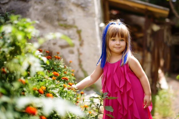 Funny toddler girl near the flowers next to the house