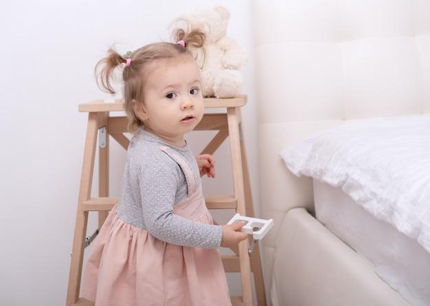 화이트 룸에서 집에서 장난감을 가지고 노는 재미 유아 소녀.