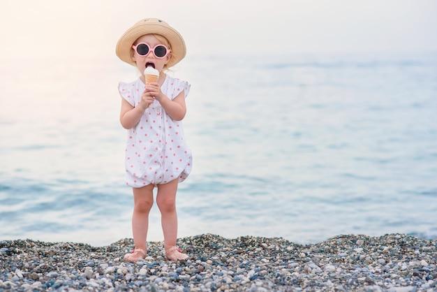 Смешная малышка в розовых летних комбинезонах, шляпе и розовых очках ест ванильно-белое мороженое на каникулах на морском пляже.