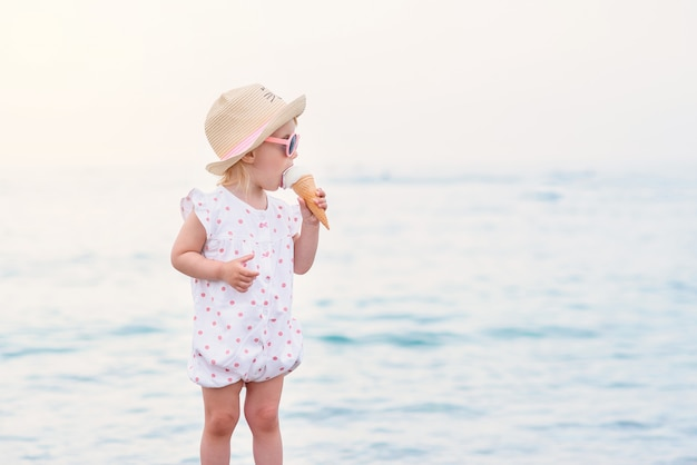 Funny toddler girl wearing pink summer overalls, hat and pink sunglasses eats vanilla white ice cream on the vacations on the sea beach.