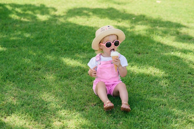Funny toddler girl wearing pink summer overalls, hat and pink sunglasses sits on a green lawn eats vanilla white ice cream in a sunny garden.
