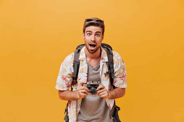 Funny tourist with blue eyes in sunglasses, fashionable summer shirt and grey plaid t-shirt looking into camera on orange wall