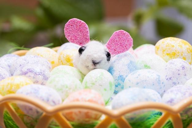 Забавный игрушечный заяц с крашеными пасхальными яйцами в корзине. фото высокого качества