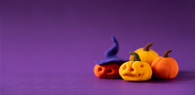 Funny toy pumpkins from plasticine molded children. scary halloween with open space for text.