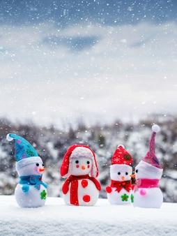 눈이 내리는 동안 열린 공간에서 재미있는 장난감 눈사람. 크리스마스와 새 해 인사말 카드