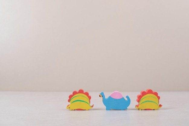 Funny toys of dinosaurs on beige space.