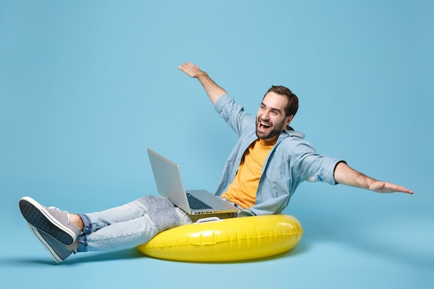 파란색 벽에 고립 된 노란색 옷에 재미있는 여행자 관광 남자. 주말에 해외로 여행하는 승객. 항공 비행 여행 개념. 노트북에 풍선 링 작업에 앉아 손을 펼칩니다.