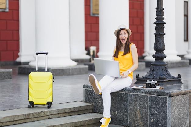 캐주얼한 옷을 입고 여행가방을 들고 모자를 쓴 재미있는 여행자 관광 여성은 도시 야외에서 노트북 컴퓨터를 사용하여 앉아 있습니다. 주말 휴가에 해외 여행을 하는 소녀. 관광 여행 라이프 스타일.
