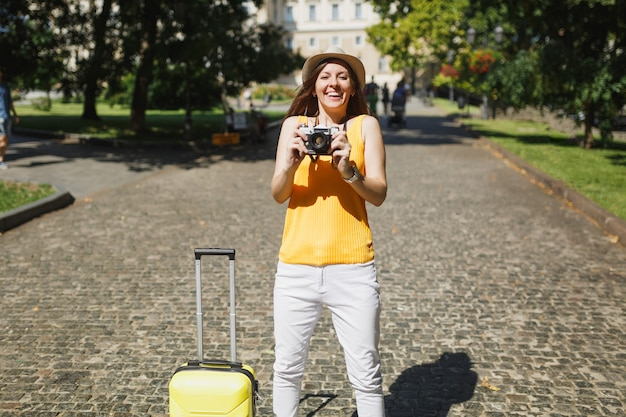 Funny traveler tourist woman in yellow casual clothes and hat with suitcase taking pictures on retro vintage photo camera outdoor. girl traveling abroad on weekend getaway. tourism journey lifestyle.