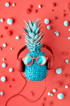 Funny turquoise pineapple in sunglasses and earphones on decorated red paper