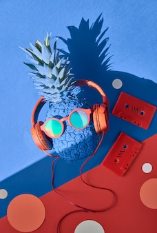 Funny turquoise pineapple in sunglasses and earphones with a shadow on blue and red paper
