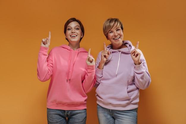 Divertenti due signore con acconciatura corta e fresca in moderne felpe con cappuccio rosa e jeans che mostrano i pollici in su su sfondo arancione isolato.