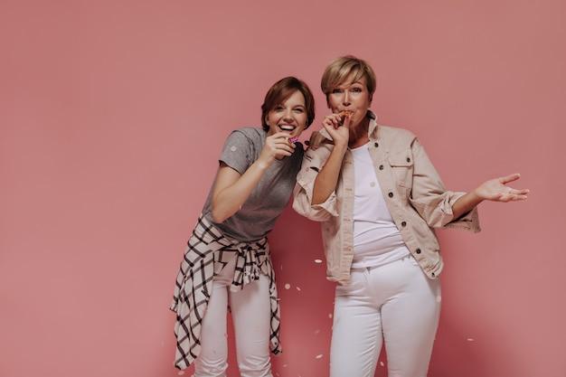 カメラを覗き込んでいる明るいモダンな服を着た短いクールな髪型の面白い2人の女性。ピンクの背景に紙吹雪で笑ってポーズ。
