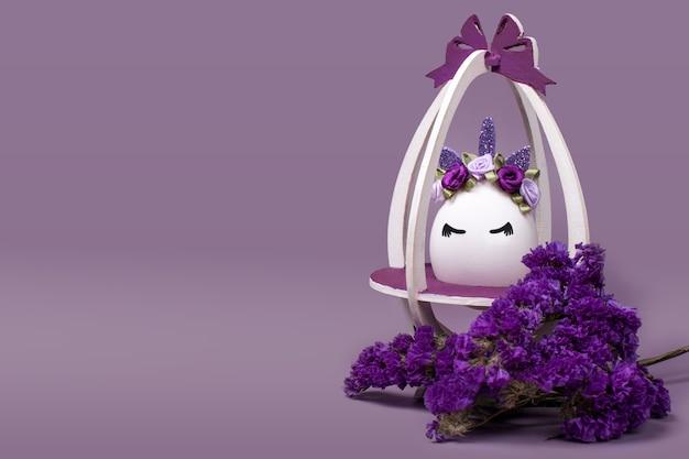 라벤더 바탕에 보라색 꽃과 함께 재미있는 유니콘 장식 달걀