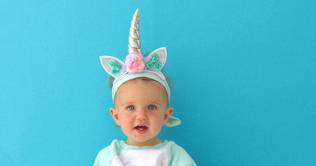 Funny unicorn little girl on blue background