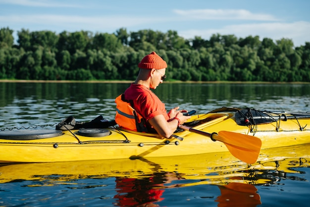 Funny unperturbed mature man in orange watch cap texting while riding on kayak